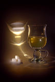 Light, glass, tea and sugar (black key still life) Stock Images