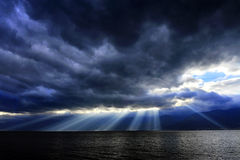The Light of God. Heavy clouds hanged low over the lake, but the sunbeam broke through rifted clouds. This natural phenomenon is called the Tyndall effect Royalty Free Stock Photos