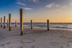 The light of golden hour at the beach with wooden piles and hearts drawings in the sand. Petten, Holland, North Sea Stock Image