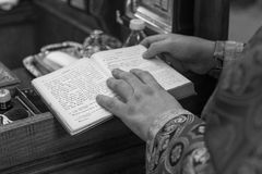 An Orthodox priest reads from the Bible during a Christian ritual in a small church. stock photos