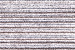 Light gray background of a knitted textile material. Fabric with a striped texture closeup. Stock Photos