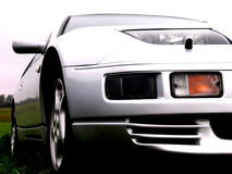 Light gray car. Closeup of a grey sports car, low angle, front corner Stock Image