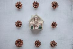 Holidays, winter and celebration concept - Christmas composition. pine cones, toy house in the center on cement royalty free stock photo