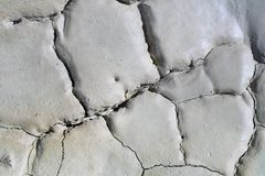 Light gray dry cracked surface of volcanic earth turned into desert. Detailed natural background, texture taken in environment in crater of active volcano royalty free stock image