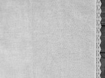 Light gray fabric from flax coarse burlap. On a gray wooden background light gray fabric from flax coarse burlap candle with white lace handmade Stock Photo