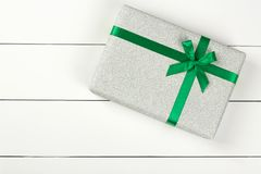 Gray glitter gift box with green ribbon isolated on white wooden background. stock image