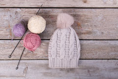 Light gray handmade knitted hat on retro boards. Stock Image