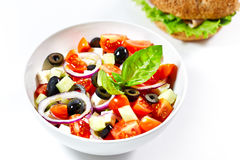 Light greek salad with fresh vegetables and burger in back Stock Photo
