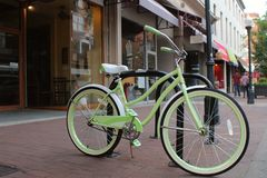 Light green bicycle beside the street on a sidewalk in the shopping district of a charming town. stock photos