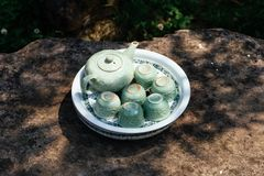 Light green ceramic tea set including jar, cups and plate on stone table under tree shadow  at Ham Rong Mountain Park in Sa Pa. Vietnam Royalty Free Stock Photos