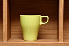 Light green coffee cup on wooden shelf. Still life depicting light green coffee cup placed on a brown wooden shelf Royalty Free Stock Images