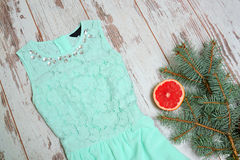 Light green dress on a wooden background, fir branch and grapefruit. Fashionable concept, christmas holidays Stock Photo