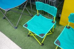 Light green foldable chairs on artificial green grass royalty free stock image