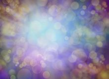 Gold purple blue green bokeh light burst background stock photography