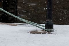 Light Green Rope. A canal barge is moored up in the snow using a light green rope Stock Image