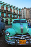 Light green vintage classic yank tank Cuban taxi car of Cuba in front of old building in Havana