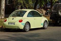 Light green Volkswagen New Beetle car parked in a street Stock Image