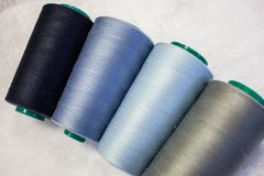 Four spools of cold colors: gray, blue and light blue. Sewing production and home crafts stock images
