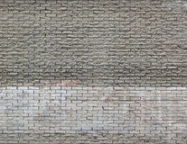 Light grey brown brick wall background with white painted stripe. Light grey brown brick wall background with white paler stripe and repeating pattern royalty free stock photo