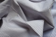 Light grey checkered fabric in soft folds Royalty Free Stock Image