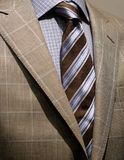 Light grey checkered jacket, blue shirt and tie. Close-up of a light grey checkered jacket with blue checkered shirt, and striped blue & black tie stock photo