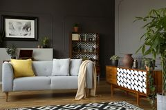 Light grey sofa with blanket and pillows. Standing in real photo of open space sitting room interior with wainscoting on the wall and retro cupboards stock images