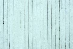 Light grey wooden background with peeling paint from long boards arranged vertically. old painted wooden boards