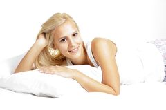 Light hair female model, relaxing in the bed Stock Images