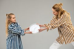 Light-haired resolute girls in striped shirts competing for usual white clock. Pulling clock over. Light-haired resolute girls in striped shirts competing for stock photo