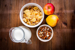Light healthy breakfast: cornflakes, milk, apples and nuts. For them. On wooden rustic table, top view, copy space Royalty Free Stock Photo