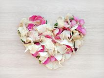 Light heart shape from pink and white rose and orchid petals on wooden background. Love and romance concept royalty free stock images