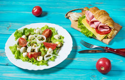 Light and hearty spring breakfast. Croissant with ham, cheese, fresh tomatoes and salad with Mozzarella on a wood table. Stock Image
