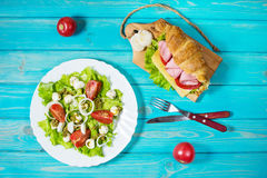 Light and hearty spring breakfast. Croissant with ham, cheese, fresh tomatoes and salad with Mozzarella on a wood table. Royalty Free Stock Photos
