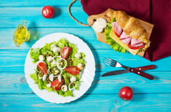 Light and hearty spring breakfast. Croissant with ham, cheese, fresh tomatoes and salad with Mozzarella on a wood table. Royalty Free Stock Image