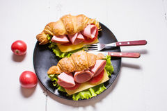 Light and hearty spring breakfast. Croissant with ham, cheese, fresh tomatoes on a white stone table Royalty Free Stock Image