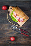 Light and hearty spring breakfast. Croissant with ham, cheese, fresh tomatoes on a wood stone table Royalty Free Stock Photography