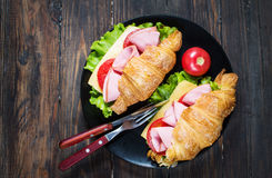 Light and hearty spring breakfast. Croissant with ham, cheese, fresh tomatoes on a wood stone table Stock Image