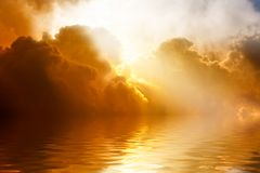 Light from heaven. Dramatic bright beams from clouds with reflection in water Royalty Free Stock Images