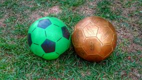 Light and heavy balls. Two soccer or football balls, plastic and leather Royalty Free Stock Photography