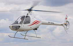 Light helicopter Guimbal Cabri G2 flying over cloudy sky Stock Image