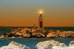 Light House. A man standing next to a small light house after sunset Stock Images