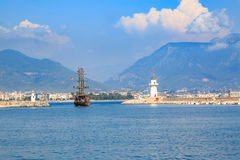 Light house in Alanya with black ship during day time Royalty Free Stock Image