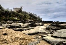 Light house & Beach Rocks Stock Photo