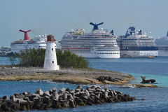 Light House and Cruise ships. This is a  working lighthouse at the end of a bay at Nassau, Bahamas; it is dwarfed by the cruise ships Royalty Free Stock Images