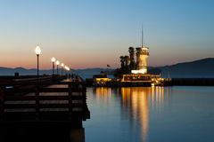 Light house with integrated restaurant at the end. Lighted tower beacon with restaurant next to a catwalk at dawn with nice mirroring in the water Stock Photography