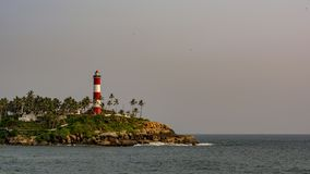 Light house at Kovalam, Trivandrum - Daylight. Lighthouse at Kovalam in daylight. Surrounded by the rocks, slopes, coconut trees and meadows royalty free stock images