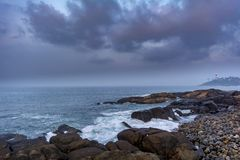 Kovalam Seascape at Trivandrum. Rocks, Pebbles, boulders, waves, clouds, sky and the light house visible on the right royalty free stock photo