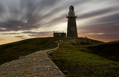 Light house with moving clouds during sunset Royalty Free Stock Photography