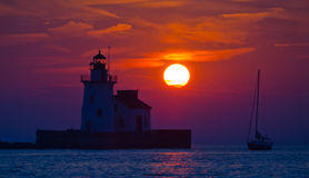 Lighthouse sailboat sunset. Night time photo purposely dark to highlight the large sun, lake erie ohio royalty free stock photos