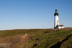 Light House. A simple yet beautiful lighthouse sits on top of a grassy field along the coast Royalty Free Stock Photo